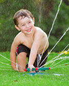 Young boy off by playing in water sprinkler — Stock Photo