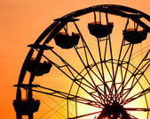 Silhouette of ferris wheel at sunset at county fair. — Stock Photo