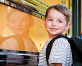 Young boy with nervous smile waits to board bus on first day of school. — Stock Photo