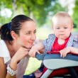 Mother with baby in stroller — Stock Photo