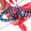 Blue strung beads and red leafs — Stock Photo