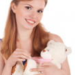 Smiling girl with teddy bear in hands — Stock Photo