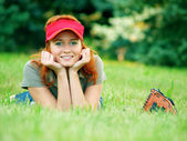 Young female laying on the gras with mitts. — Stock Photo