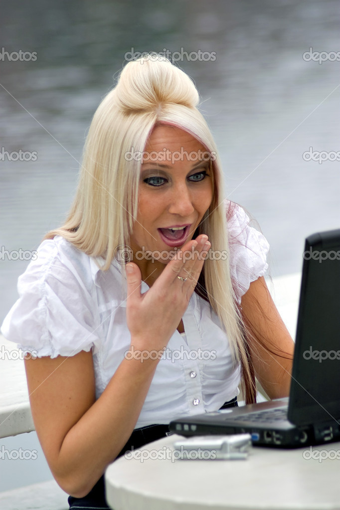 A beautiful young blonde woman is shocked by what she is seeing on her laptop screen.  It looks as if she is possibly seeing something offensive. — Stock Photo #6670679