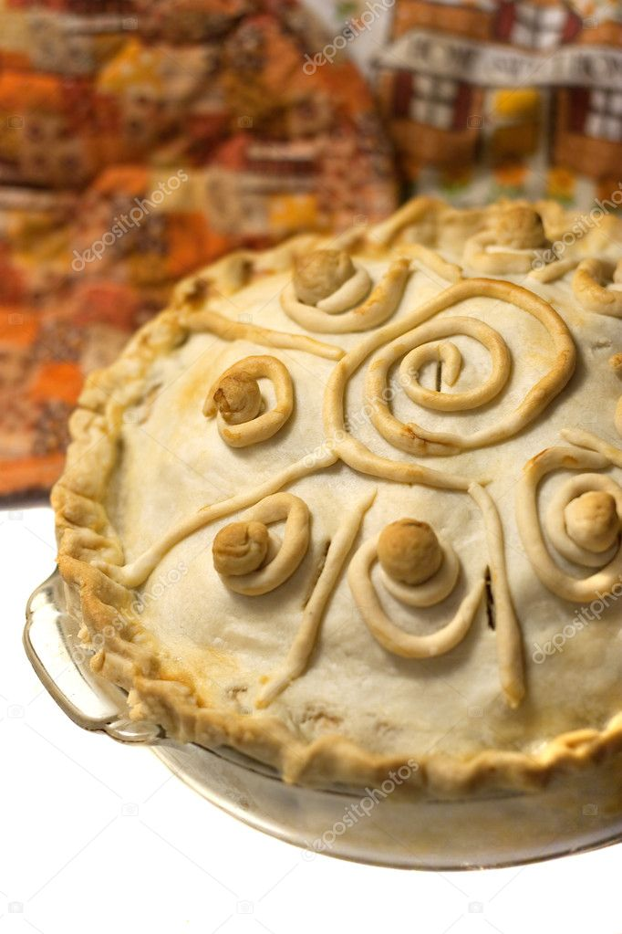 A homemade baked apple pie with custom swirl designs on the crust. — Stock Photo #6674564