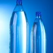 Two plastic bottles of water on blue background — Stock Photo