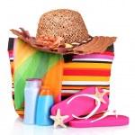Bright striped beach bag and beach items — Stock Photo