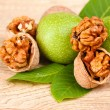 Walnuts and leaves on wooden — Stock Photo