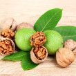 Stock Photo: Walnuts and leaves on wooden