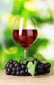 Ripe grapes and glass of wine on green background — Stock Photo