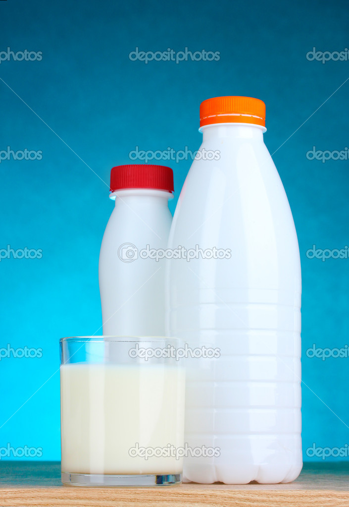 Tasty milk in glass and bottle on blue background  Stock Photo #6659763
