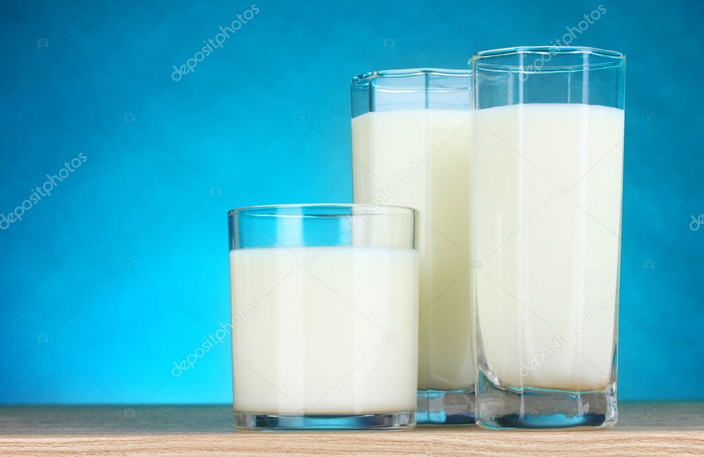 Tasty milk in glasses on blue background — Stock Photo #6659765