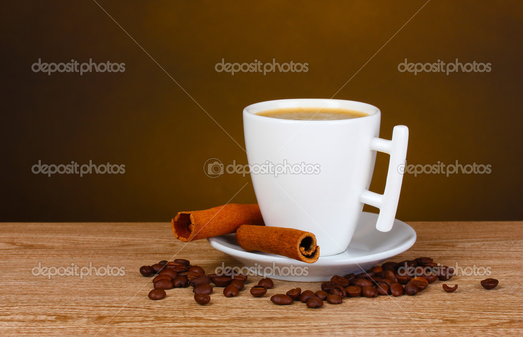 Cup of coffee, coffee beans and cinnamon on wooden table on brown background — Stock Photo #6659860