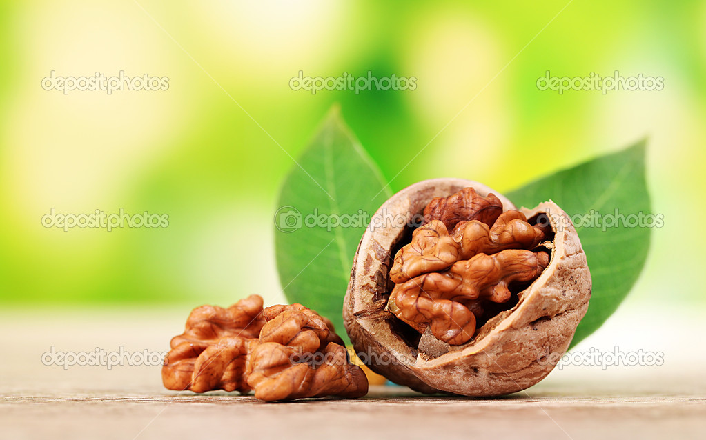 Walnuts and leaves on wooden table on green background — Stock Photo #6659999