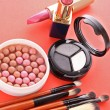 Many cosmetics on red background — Stock Photo