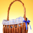 Wicker basket  on yellow background — Stock Photo