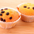 Muffins with raisins on wooden surface — Stock Photo