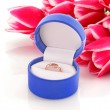 Gold engagement ring in box on the flowers background — Stock Photo #6661379