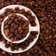 Small white cup of coffee with coffee grain on grain background - Zdjęcie stockowe