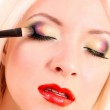 Beautiful young blonde woman with bright make-up and brush on w — Stock Photo #6662032