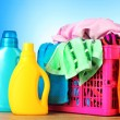 Royalty-Free Stock Photo: Bright clothes in a laundry basket on blue background