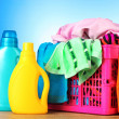 Bright clothes in a laundry basket on blue background — Stock Photo