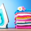 Pile of colorful clothes and electric iron on blue background — 图库照片 #6668224