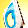 Electric iron on the yellow background - Stock Photo