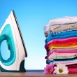 Pile of colorful clothes and electric iron on blue background — Stock Photo #6668242