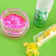 Color spangles for manicure  on green background — Stock Photo