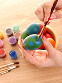 Hands hold easter eggs, color paint and brush — Stock Photo