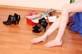 Closeup of a woman leg on floor and many shoes around — Stock Photo