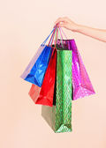 ženská ruka drží mnoho barevné nákupní tašky — Stock fotografie