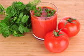Glass of fresh tomato juice and tomatoes round the glass on th — Stock Photo