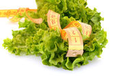 Tape measure and lettuce on white — Stock Photo