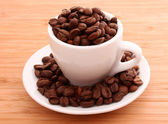 Coffee beans and a cup isolated on brawn — Stock Photo