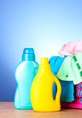 Colorful towels and liquid laundry detergent over blue — Stock Photo