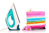 Pile of colorful clothes and electric iron over white backgroun — Stock Photo