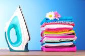 Pila de ropa colorida y plancha eléctrica sobre fondo azul — Foto de Stock