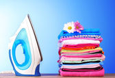 Pile of colorful clothes and electric iron on blue background — Stock Photo