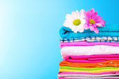Pile of colorful clothes and flowers on blue background — Stock Photo
