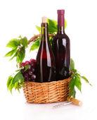 červené víno a hrozny v košíku izolované na bílém — Stock fotografie