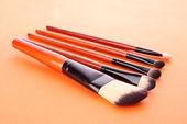 Cosmetic brushes on orange background — Stock Photo