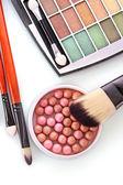 Cosmetic brushes brush , eye shadows and rouge on the orange b — Stock Photo