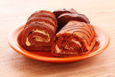 Swiss roll on the dish on wooden background — Stock Photo