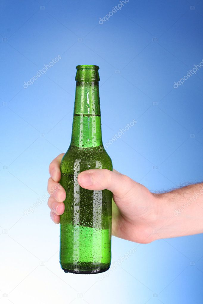 Bottle of beer in hand on blue background — Stock Photo #6660866