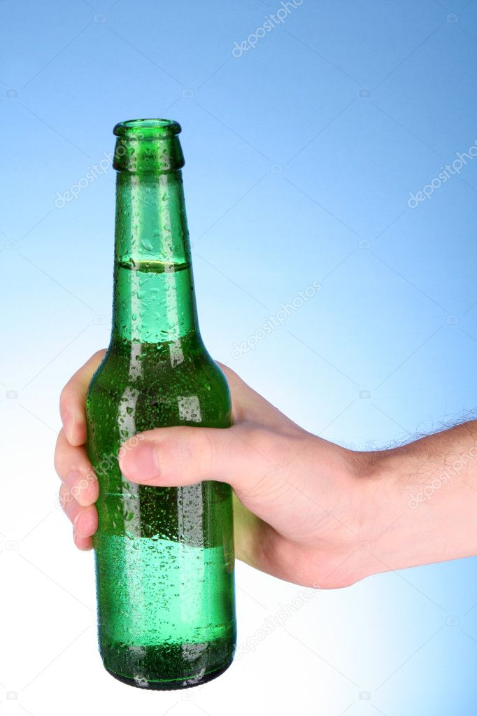 Bottle of beer in hand on blue background — Stock Photo #6660872