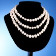 A pearl necklace on a blue background - Stock Photo