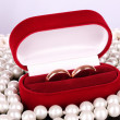 Stock Photo: Wedding rings in a box and pearls