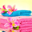 Stacked colorful towels on yellow background — Stock Photo #6676709